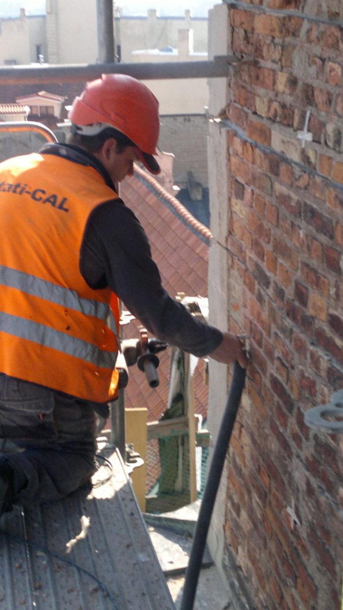 Vysávání drážek na štítové zdi kostela pro helikální výztuž